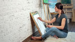 Talented female painter making graphic picture on canvas using pencil full shot. Barefoot focused young creative woman drawing at art studio sitting on floor stock footage
