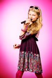 Talented girl. Little modern girl in beautiful dress singing into a microphone over pink background Royalty Free Stock Photography