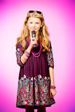 Talented girl. Little modern girl in beautiful dress singing into a microphone over pink background Stock Photo