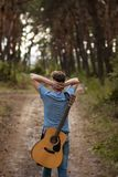 Talented guitarist playing forest hiking concept. Stock Image