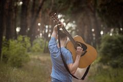 Talented guitarist playing forest hiking concept. Happiness of the artist. Unity with the nature Stock Photo