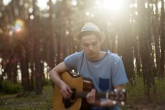 Talented guitarist playing forest hiking concept. Lifestyle of the artist. Unity with the nature stock photo