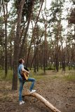 Talented guitarist playing forest hiking concept. Royalty Free Stock Photography