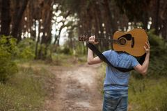Talented guitarist playing forest hiking concept. Royalty Free Stock Photo