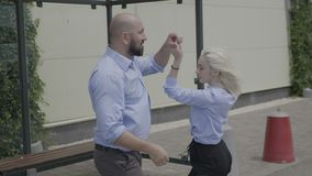 Talented happy couple dancing salsa on street while they waiting for a bus outside in the public bus station. -. Talented happy couple dancing salsa on street stock video footage