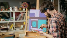 Artist Paints Modern Artwork. Talented inspired artist painting modern artwork, fair haired man making orange lines with paintbrush on aqua background, working stock footage