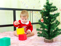 Talented little boy builds new year tower. From plastic bricks near Christmas tree Stock Image