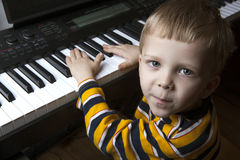 Talented little boy sitting at the piano Stock Photography