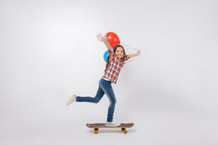 Talented little child skateboarding in the studio. Demonstrating new skills. Skilled gifted happy child expressing joy and holding colorful balloons while Stock Photos