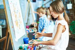 Talented Little Girl in Art Studio. Side view portrait of talented teenage girl painting beautiful picture on easel in art class, working with other children stock photography