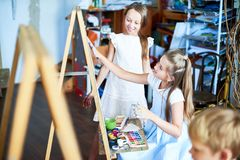 Talented Little Girls in Art school. Portrait of pretty girl painting picture on easel in art class, with other children watching her, copy space stock photos
