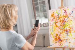 Talented mature woman taking photo. Sharing my masterpiece. Creative attractive mature woman storying memory while rising phone and posing from back royalty free stock image