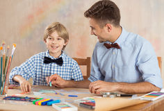 Talented pupil with teacher. Picture of happy talented pupil drawing together with his teacher Royalty Free Stock Image