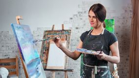 Talented relaxed young female painter enjoying drawing picture on canvas using brush medium shot. Woman artist wearing apron creating beautiful painting on stock footage