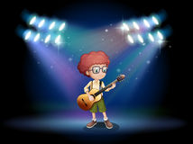 A talented teenager in the middle of the stage with a guitar Stock Images