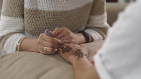 Talented woman is painting female hands by henna mehndi decorations stock video footage