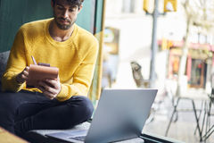 Talented young male journalist working on his new book. Review writing composition in notebook starting working day with hot cafe in cozy coffee shop getting Royalty Free Stock Image