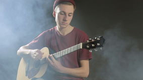 Talented young musician playing guitar in a dark stock footage