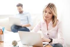 Talentierte blonde Frau, die Computer für Arbeit verwendet Lizenzfreies Stockfoto