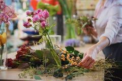 Talentierter Florist, der Blumenstrauß in der Werkstatt macht Stockfotografie