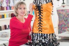 Talentierter weiblicher Dressmaking, der Knöpfe auf Kleidung justiert stockfoto