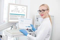 Talentierter weiblicher Forscher, der mit moderner Technologie arbeitet Stockbild