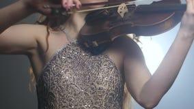 Talento musical, mujer hermosa en el vestido chispeante con el fiddler en la iluminación del reflector metrajes
