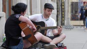 Talentos de la calle, juego de la juventud en el instrumento atado que se sienta en el betún en aire abierto almacen de video
