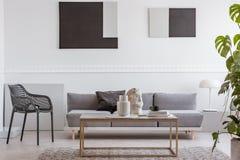 Talents de Knick sur la table basse élégante devant le sofa gris dans l'intérieur de luxe de salon photographie stock
