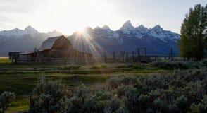Talents de Sun tombant sur la grange abandonnée dans le pré alpin Photos libres de droits