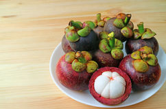 Talerz Dojrzałego Purpurowego mangostanu Całe owoc i Otwierający Pokazywać Delectable Czystego Białego mięso na Drewnianym stole Zdjęcia Royalty Free