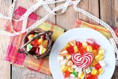 Talerz i kosz z kolorowymi słodkimi cukierkami Obrazy Stock
