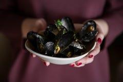 Talerz mussels w rękach kobieta Fotografia Royalty Free