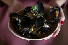 Talerz mussels w rękach kobieta z bliska Zdjęcia Royalty Free