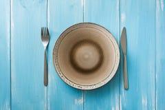 Talerz na błękitnym drewnianym tle z naczyniami Zdjęcie Stock