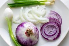 Talerz pełno siekać cebule z słodkimi cebulami, meksykańskimi cebulami i zielonymi cebulami na białym talerzu na kuchennym stole, zdjęcie stock
