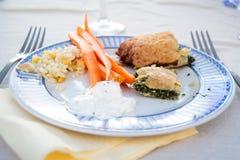 Talerz pełno wyśmienicie jedzenie i dwa rozwidlenia na stole Zdjęcia Stock