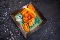 Talerz pokrojeni przekrawający śliwkowi pomidory z podprawą obrazy stock