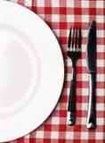 Talerz przy klasycznym w kratkę tablecloth Zdjęcia Royalty Free