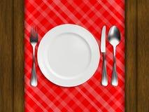 Talerz, rozwidlenie, łyżka i nóż na czerwonym w kratkę tablecloth, royalty ilustracja