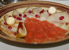 Talerz rybie zakąski Dekorujący z granatowiec pomarańcze i ziarnami zdjęcia royalty free