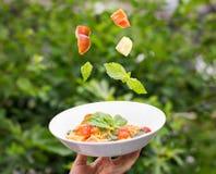 Talerz spaghetti marinara z świeżymi pomidorami i basilem zawieszającymi w powietrzu nad ono zdjęcie stock