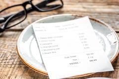 Talerz, szkła i czek na cukiernianym biurka tle, zdjęcia stock