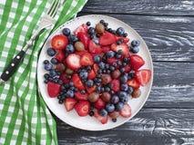 Talerz truskawki, czarne jagody, agresta produktu lato na drewnianym tle Zdjęcie Stock