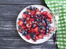 Talerz truskawki, czarne jagody, witamina przeciwutleniacza agrestów produktu wyśmienicie organicznie lato na drewnianym tle Obrazy Stock