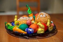 Talerz wielkanoc pełno taktuje cukierki, słodka bułeczka i barwionych jajka -, zdjęcia stock