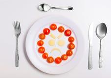 Talerz z śmiesznymi emoticons robić od jedzenia z cutlery na bielu Zdjęcia Stock