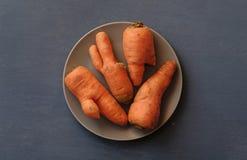 Talerz z brzydkimi marchewkami z góry zdjęcia stock