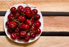 Talerz z czerwonymi wiśniami na drewnianych talerzach, odgórny widok, przestrzeń dla teksta Fotografia Stock
