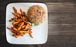 Talerz z hamburgerem i batatem smaży na nieociosanym drewnianym stole zdjęcia royalty free